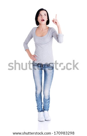 Surprised woman with opened mouth pointing up on copy space. Isolated on white background.