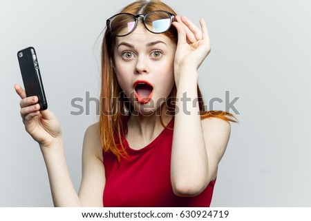 Surprised woman with phone, the woman is surprised and in shock from being informed, a woman with round eyes is looking at the camera #630924719