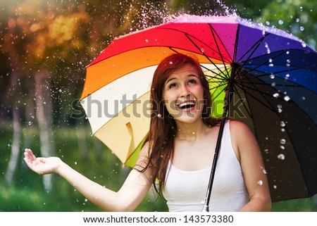 Surprised woman with umbrella during summer rain #143573380