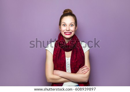 Stock Photo Surprised Woman. Young emotional beauty with collected hair and red scarf looking excited, crossed hands purple background. expressing positive emotions, smile with big eyes and teeth.