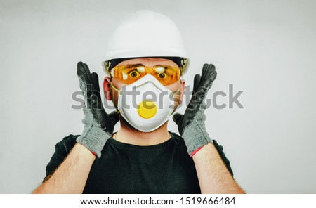Surprised worker wearing a protective helmet, protective goggles and a protective mask. Concept of work surprise, hiring workers for construction. Preparation to work.