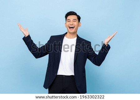Surprised worry free handsome Asian man in semi formal clothes smiling and opening hands in light blue isolated studio background