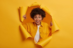 Surprised young African American woman stands in torn paper hole, dressed in stylish clothes, has excited cheerful expression, looks through breakthrough of yellow background. Wow, great news