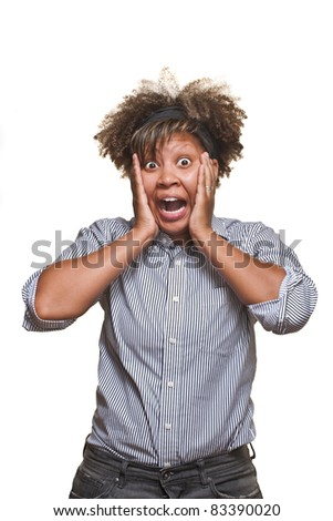 Surprised young African girl poses in front of white background. - stock photo