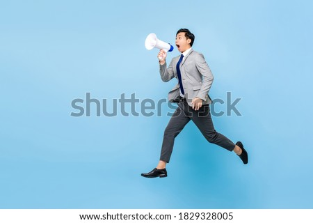 Surprised young Asian businessman jumping and shouting on megaphone isolated on light blue background with copy space Photo stock ©