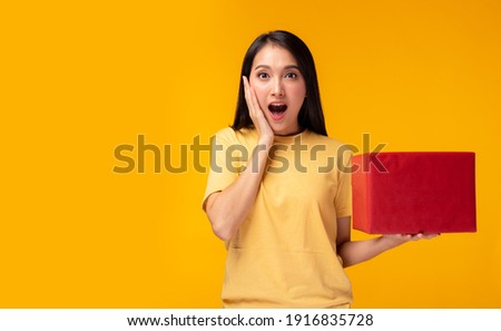 Surprised young asian woman holding red gift box and get shock by open mouth Standing over yellow background Beautiful Asia girl happy smile hold new year gift box present Using for advertisement