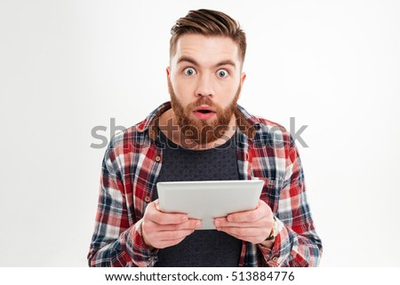 Surprised young bearded man in plaid shirt holding tablet over white background #513884776
