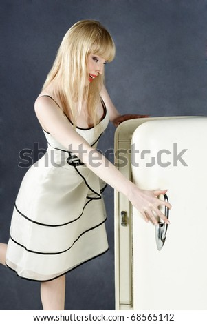 Surprised young blond woman looking into open refrigerator