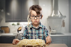 Surprised young boy in glasses with spaghetti