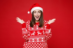 Surprised young brunette Santa woman in sweater, Christmas hat keeping mouth open spreading hands isolated on red colour background, studio portrait. Happy New Year celebration merry holiday concept