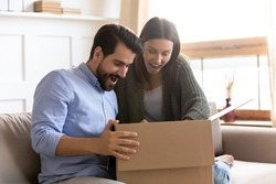 Surprised young clients looking inside cardboard box, satisfied with ordered item. Happy smiling family couple opening carton parcel in living room, amazed by fast delivery high quality service.