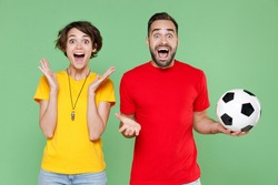 Surprised young couple friends sport family woman man football fans in t-shirts cheer up support favorite team with soccer ball keeping mouth open spreading hands isolated on green background studio