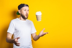 Surprised young guy in white t-shirt catches paper cup on yellow background.