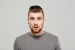 Surprised young handsome man posing over grey background. Copy space.