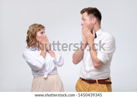 Surprised young man and mature woman looking at each other in full disbelief, having astonished amazed looks. Studio shot