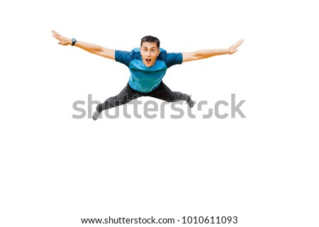 surprised young man flies in widely separated hands isolated on white. Concept fitness or trampoline center #1010611093