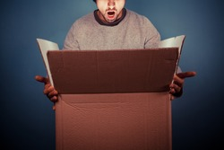 Surprised young man is opening a large cardboard box with something exciting inside it