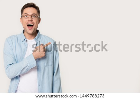 Photo of Surprised young man showing by forefinger at blank copy space. Stunned, amazed, astonished male standing pointing aside with index finger wearing glasses looking at camera isolated on gray background