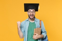 Surprised young man student in graduation cap glasses backpack hold books isolated on yellow background. Education in high school university college concept. Mock up copy space. Doing winner gesture