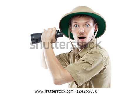 Surprised young man wearing a pith helmet and holding binoculars, isolated on white