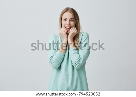 Surprised young pretty female with long blonde hair, looks with opened mouth at camera, excited to see something pleasant, dressed casually. Surprisment and facial expression #794523052