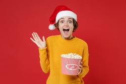 Surprised young Santa woman in casual yellow sweater Christmas hat hold bucket of popcorn spreading hands isolated on red background studio portrait. Happy New Year celebration merry holiday concept