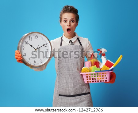surprised young scrubwoman in apron with a basket with cleansers, brushes and clock isolated on blue background. Enjoy a sparkling clean home. But cleaning should plan in advance