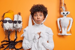 Surprised young woman dressed like mummy or ghost celebrates halloween afraids of something scarying poses against orange background creepy creatures near. Ethnic female in carnival costume.