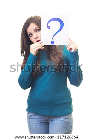 Surprised young woman in a blue shirt holding a poster with a big question mark. Isolated on white background