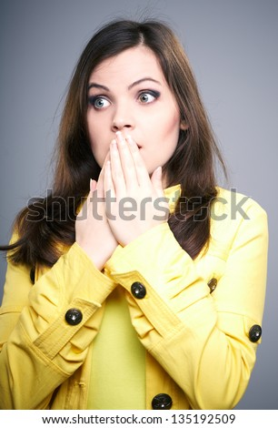 Surprised young woman in a yellow jacket. Looking to the right. Covers her mouth with her hands. On a gray background