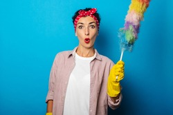 Surprised young woman in gloves holding dust brush on blue background.