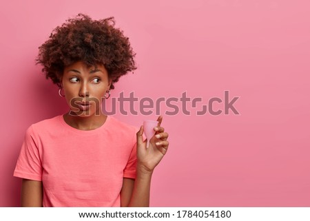 Surprised young woman poses with feminine hygiene device that is inserted in vagina during menstruation. Female holds menstrual cup to collect menstrual fluid and prevent its leaking on clothes