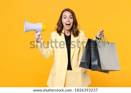 Surprised young woman 20s wearing basic light suit jacket hold package bags with purchases after shopping megaphone looking camera isolated on yellow background, studio portrait. Black friday sale