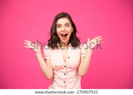 Surprised young woman shouting over pink background. Looking at camera