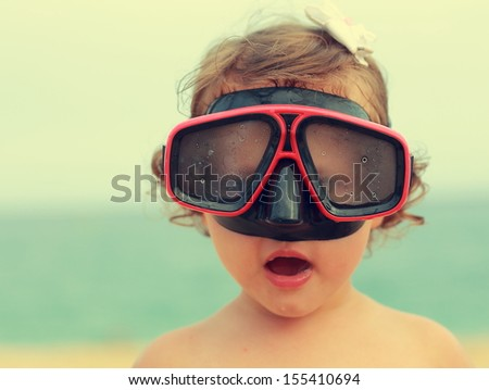 Surprising baby girl in diving mask looking fun on blue sea background