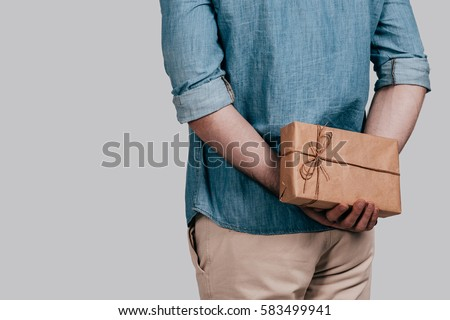 Surprising her... Close-up rear view of man in blue jeans shirt holding a gift box behind his back while standing against grey background ストックフォト ©