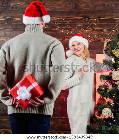 Surprising his wife. Giving and sharing. Generosity and kindness. Prepare surprise for darling. Winter surprise. Man carry gift box behind back. Woman smiling face santa. Christmas surprise concept.