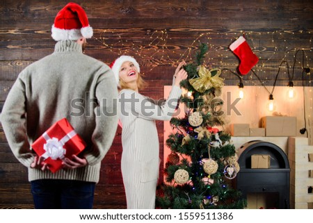 Surprising his wife. Prepare surprise for darling. Winter surprise. Man carry gift box behind back. Woman smiling face santa. Christmas surprise concept. Giving and sharing. Generosity and kindness.