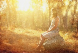 surreal blurred background of young woman sitting on the stone in forest. abstract and dreamy concept. image is textured and retro toned
