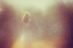 surreal blurred background of young woman stands in forest. abstract and dreamy concept. image is textured