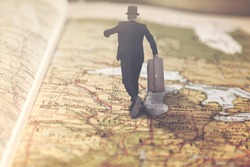 surreal businessman runs over a giant map towards a lucrative job