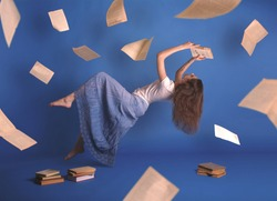 Surreal creative design, levitation. Flying woman. Levity people. Reading girl. Pages of books flying in the air. Floating in the air magic book.