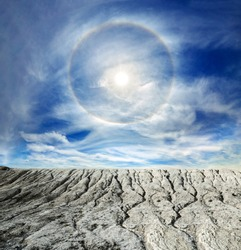 Surreal fantasy extraterrestrial landscape. Digitalart artwork. Sun halo in the blue sky around the sun over the white cracked mountains. Natural phenomenon