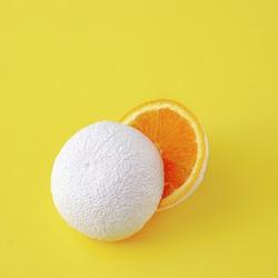 Surreal idea of unreal white cut orange fruit on yellow background.
