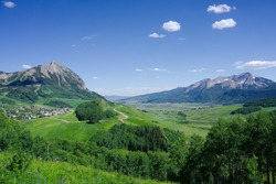 Surreal Landscape View of Stunning Mountain Peaks with Peaceful Town Below. Beautiful View of the Mt. Crested Butte Village and the Town of Crested Butte, CO. Expansive View of Mountain Town.