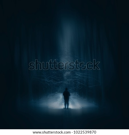 Surreal night forest landscape with alone strange man with flashlight. Horror scene.