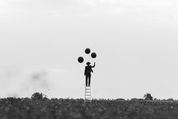 surreal photo of a single man in a suit on a staircase with balloons in a field. Concept of freedom and independence