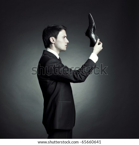Surreal portrait of a stylish man in an elegant suit and shoes in hand - stock photo