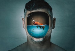 Surreal portrait of man with cropped face filled with water with a fish inside on a blue background. Surreal image. Surrealism.