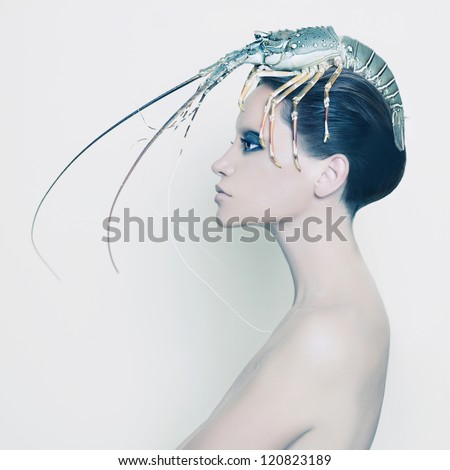 Surreal portrait of young lady with lobster on her head